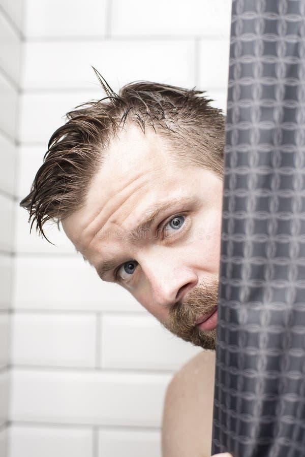 Den stiliga skäggiga mannen med vått hår ser bakifrån en gardin royaltyfri fotografi