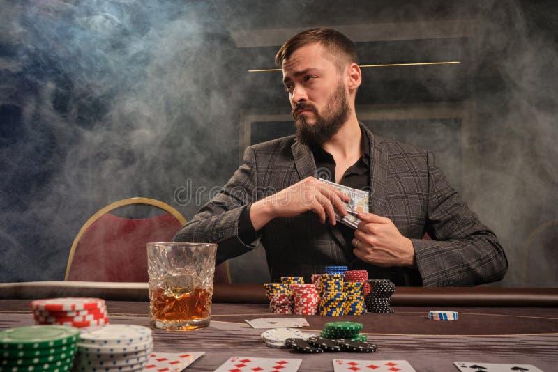 Den stiliga skäggiga mannen spelar poker som sitter på tabellen i kasino arkivfoton