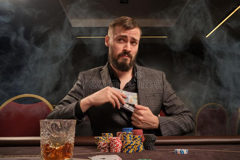 Den stiliga skäggiga mannen spelar poker som sitter på tabellen i kasino royaltyfri fotografi