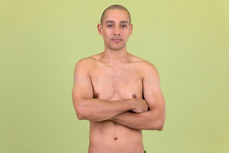 Den stiliga skalliga mång- etniska mannen med armar korsade shirtless royaltyfri fotografi