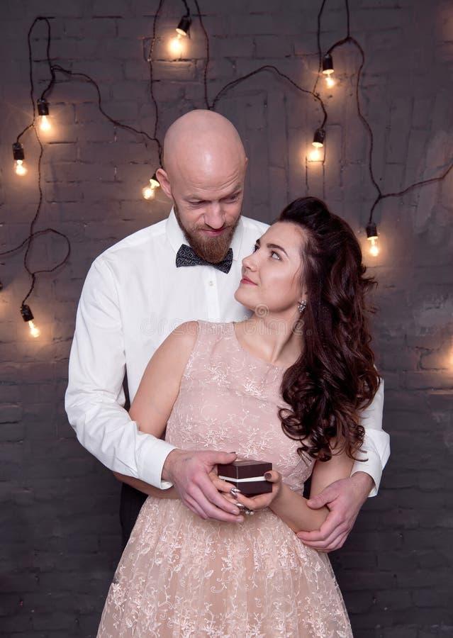 Den stiliga skalliga mannen med ett skägg gör förslaget för hans flickvän fotografering för bildbyråer