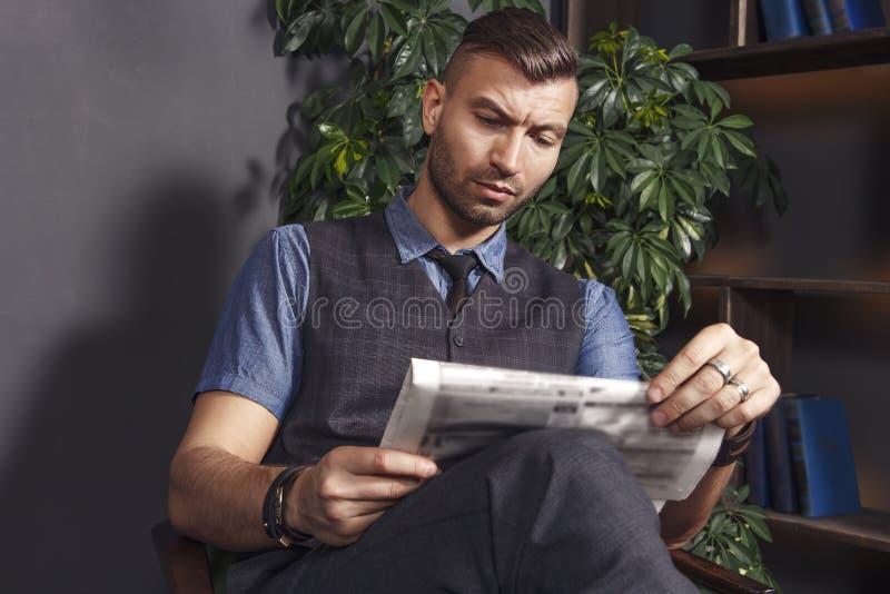 Den stiliga stilfulla mannen sitter i stol och läser senast nyheterna i tidning säker brutal affärsman i lyxiga lägenheter royaltyfria foton