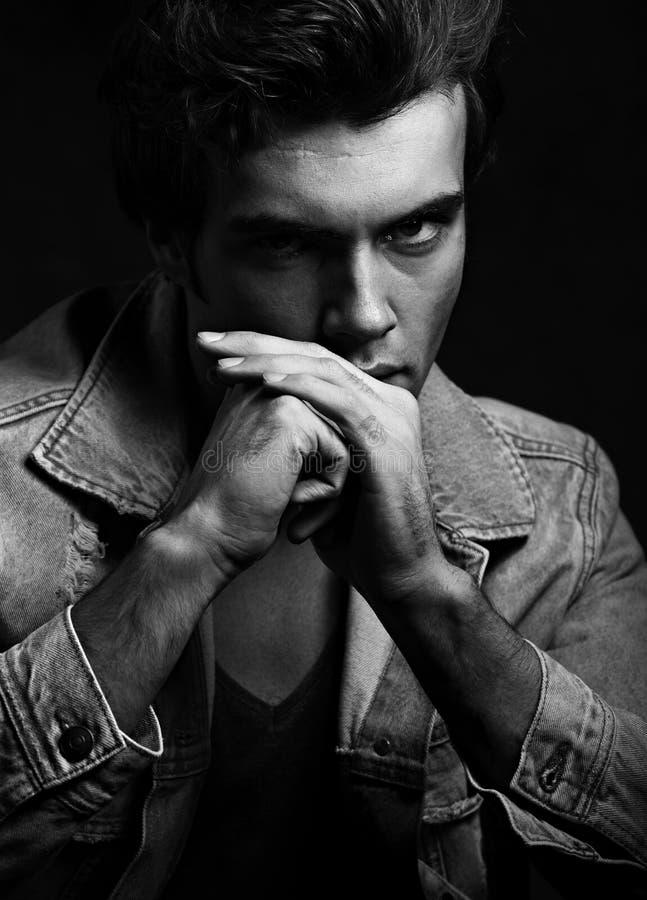 Den stiliga tänkande manliga modellen som poserar i modejeans, klår upp fotografering för bildbyråer