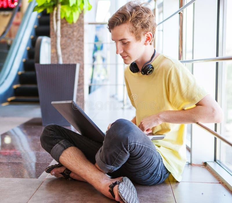 Den stiliga tonårs- pojken som använder wifiinternet, förbinder arkivbild