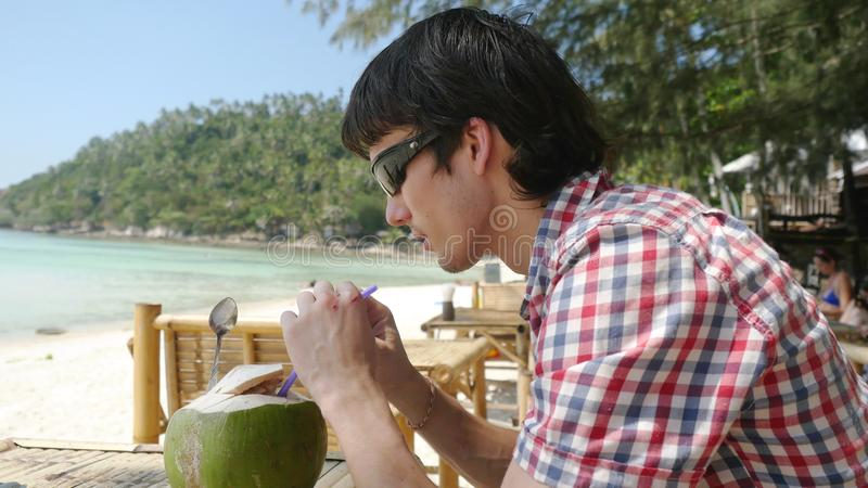 Den stiliga unga affärsmannen i solglasögon dricker på ny kokosnötfruktsaft i ett strandkafé med havssikt på palmträd royaltyfri fotografi