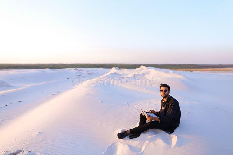 Den stiliga unga arabiska mannen skriver på internet genom att använda bärbara datorn och sitter arkivbilder