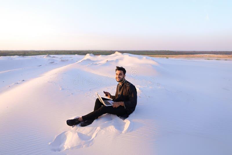 Den stiliga unga arabiska mannen skriver på internet genom att använda bärbara datorn och sitter royaltyfria bilder