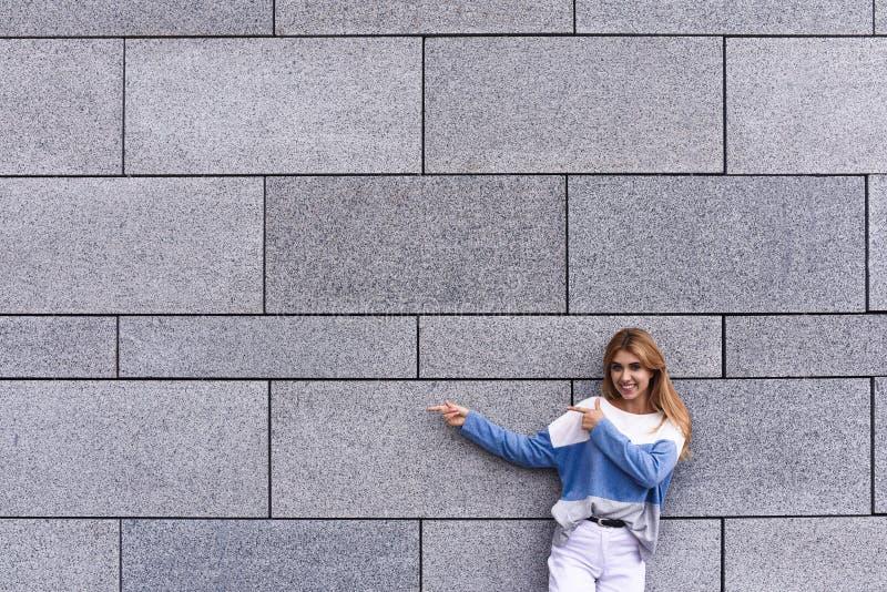 Den stiliga unga kvinnan pekar bort och att se kameran och att le som står mot den gråa väggen arkivbild