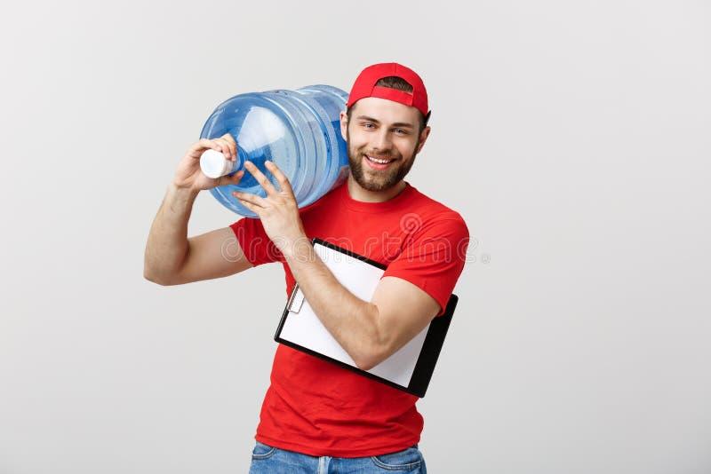 Den stiliga unga leveransarbetaren i röd likformig rymmer en flaska av vatten, ser kameran och ler, på grå färger royaltyfri fotografi