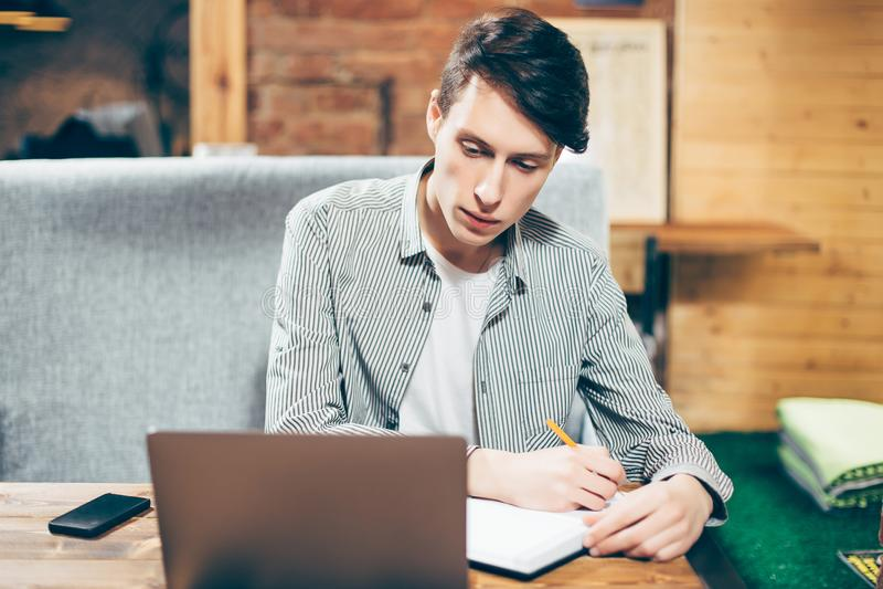 Den stiliga unga mannen använder en bärbar dator och tar anmärkningar, medan sitta i kafé royaltyfri fotografi