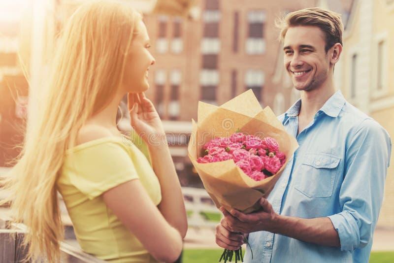 Den stiliga unga mannen ger blommor till den gulliga flickan royaltyfri bild