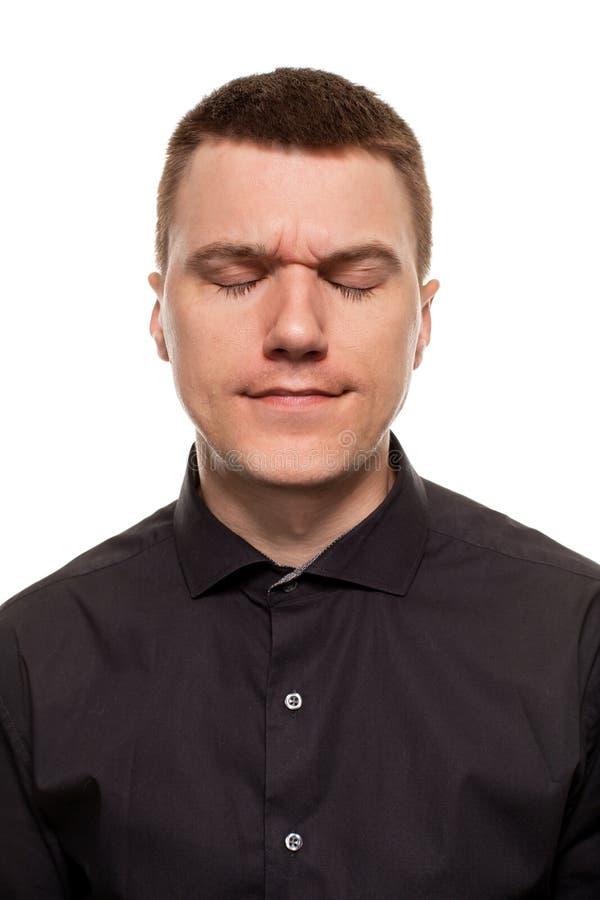 Den stiliga unga mannen i en svart skjorta gör framsidor, medan stå isolerad på en vit bakgrund arkivfoton
