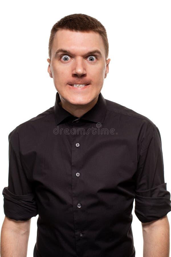 Den stiliga unga mannen i en svart skjorta gör framsidor, medan stå isolerad på en vit bakgrund arkivbild
