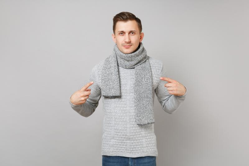 Den stiliga unga mannen i den gråa tröjan, halsduk som pekar pekfingrar på honom, isolerade på grå väggbakgrund Sunt arkivfoton