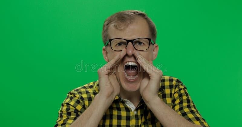 Den stiliga unga mannen i den gula skjortan fick ilsken och startade att ropa högt arkivfoto