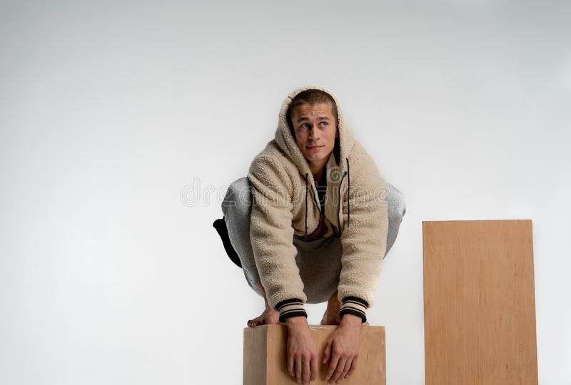 Den stiliga unga mannen i den moderiktiga sportswearen som sitter p? tr?kuben i spidermanen poserar och att se bort som isoleras  fotografering för bildbyråer
