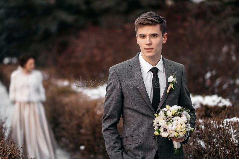 Den stiliga unga mannen med buketten i händer i vinter parkerar Hans brud står på en suddig bakgrund royaltyfri bild
