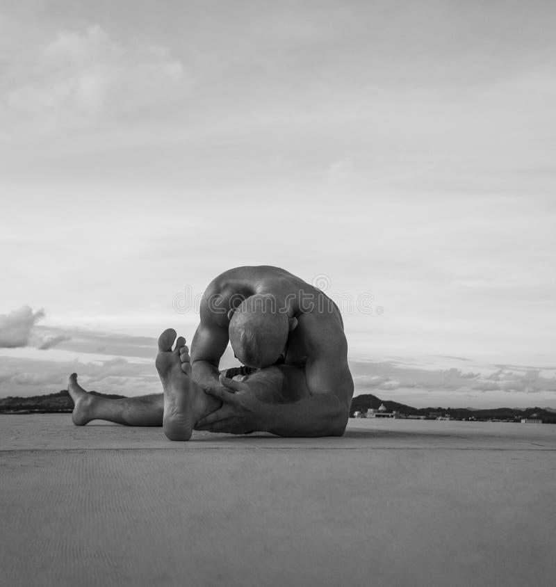 Den stiliga unga mannen med den nakna torson som gör sträckning, övar på ett tak royaltyfri fotografi