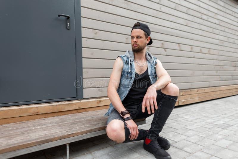 Den stiliga unga mannen med ett skägg i en moderiktig grov bomullstvill tilldelar en T-tröja i stilfull riven sönder jeans i gymn royaltyfria foton