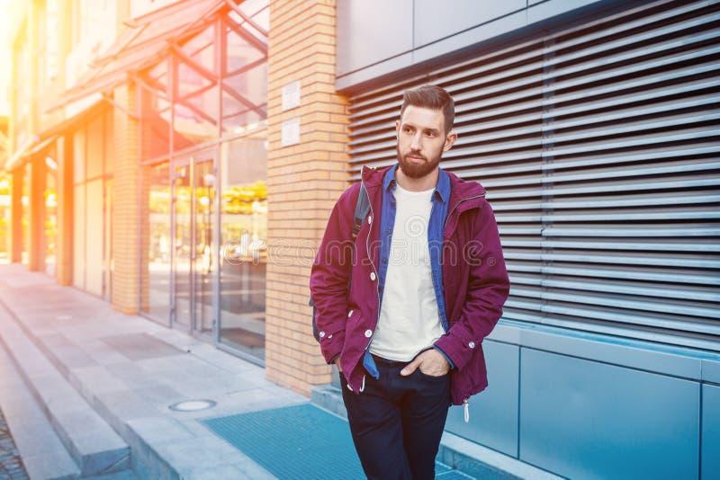 Den stiliga unga mannen med frisyren i trendig kläder står utomhus-, i stadsgata och att se från sidan Solsignalljus arkivfoto