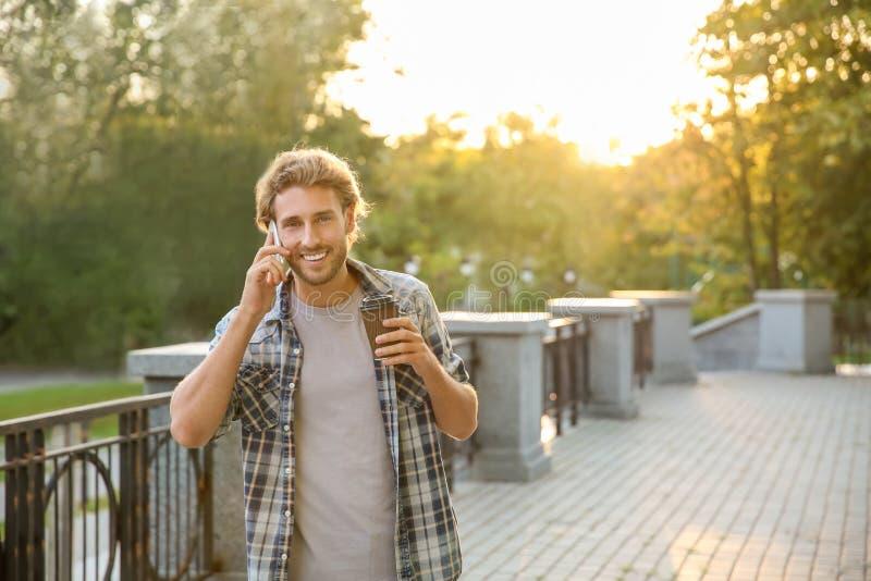 Den stiliga unga mannen med kaffe som talar på mobiltelefonen parkerar in royaltyfri fotografi