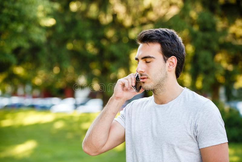 Den stiliga unga mannen parkerar in talkig på hans telefon royaltyfri bild