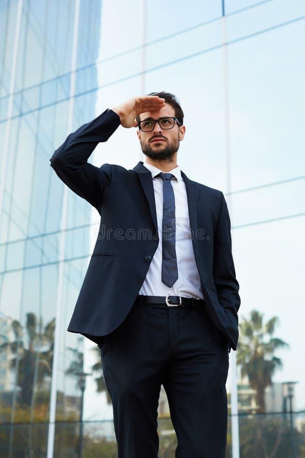 Den stiliga unga mannen ser in i avståndet som försöker att se hans flickvän royaltyfria foton