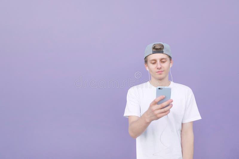 Den stiliga unga mannen som bär en vitt T-tröja och lock, lyssnar till musik i hörlurar och ser en smartphone arkivfoton