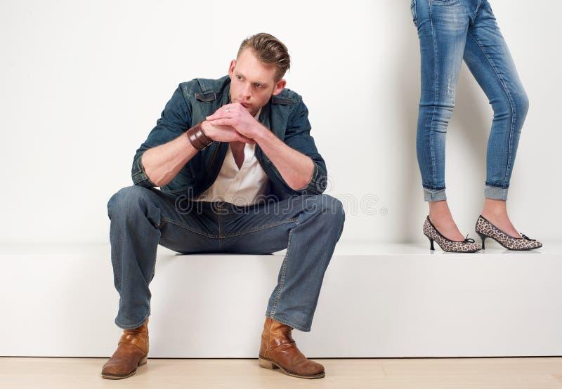 Den stiliga unga mannen som bara sitter med kvinnlign, lägger benen på ryggen anseende royaltyfria bilder