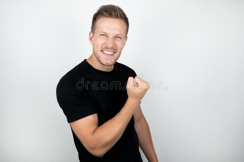 Den stiliga unga mannen som ja bär svart framgång för t-skjorta visningvinnare för att underteckna positivt le, ser lycklig isole royaltyfri foto