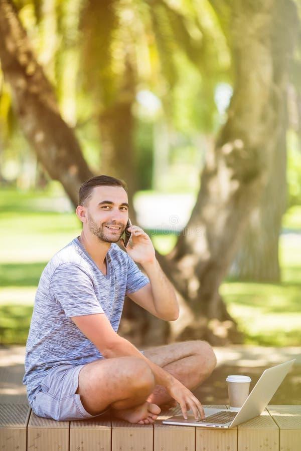 Den stiliga unga mannen som placerar på en bänk med hans bärbar dator på en gata bredvid, parkerar, medan tala på hans telefon royaltyfri foto