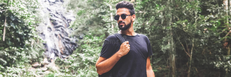 Den stiliga unga stilfulla mannen i svart t-skjorta och solglasögon kopplas in, i trekking i den gröna djungeln royaltyfri foto