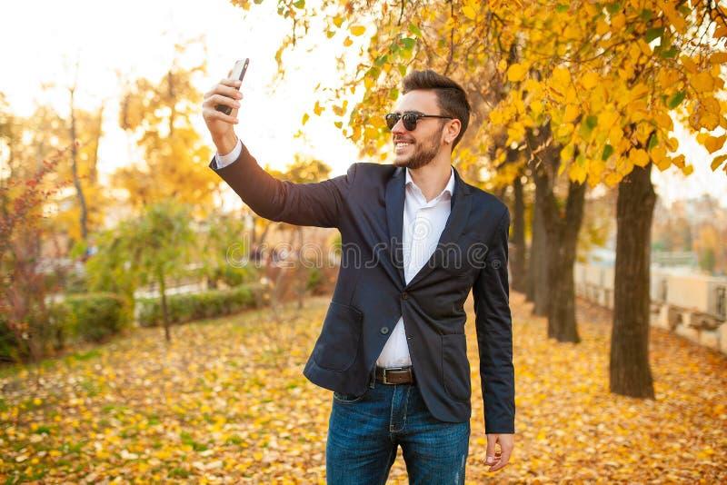 Den stiliga unga trendiga mannen i en stilfull affärsdräkt och solglasögon gör selfie arkivfoton
