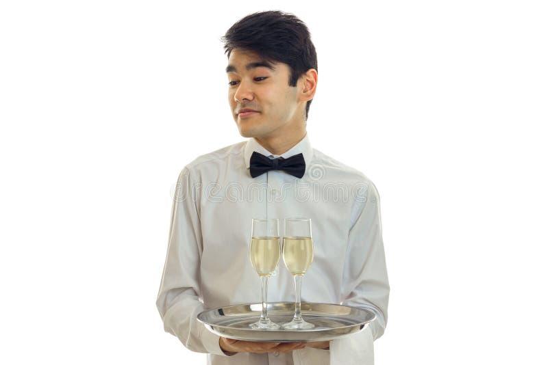 Den stiliga unga uppassaren vände hans huvud och innehav exponeringsglas för en champagne på ett magasin det fotografering för bildbyråer