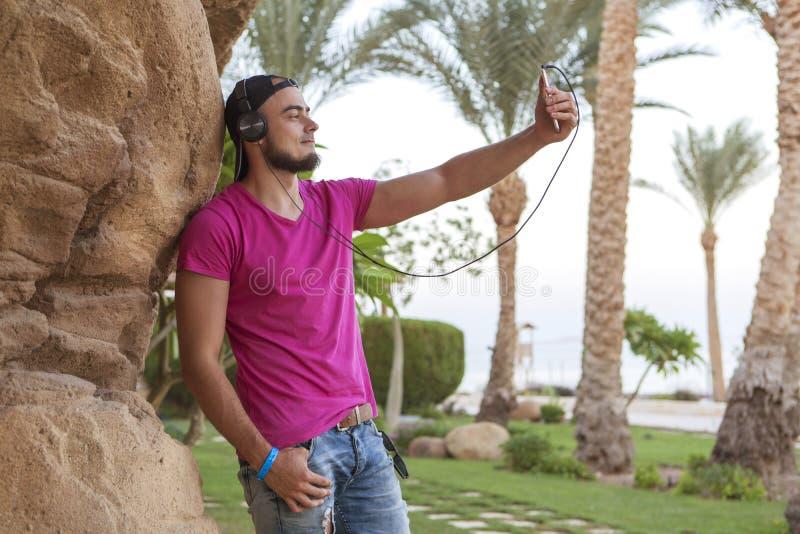 Den stiliga vuxna caucasian mannen med det svarta skägget i jeans kortsluter fotografering för bildbyråer