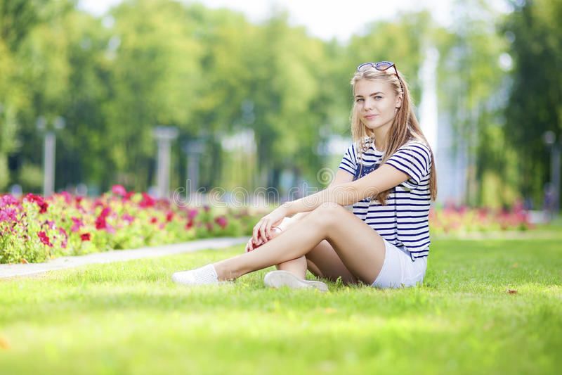 Den stillsamma Caucasian blonda tonårs- flickan som poserar på gräset i grön blommig sommar, parkerar royaltyfri foto