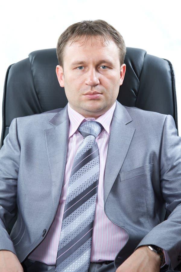 Den stolta företagsägaren poserar för en allvarlig stående på vit bakgrund. Allvarlig ung affärsman arkivbilder