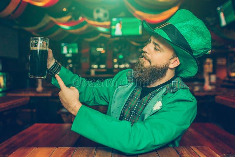 Den stolta och säkra unga mannen sitter på tabellen i bar Han rymmer rånar av mörkt öl och visar det till kameran St för kläder f arkivfoton