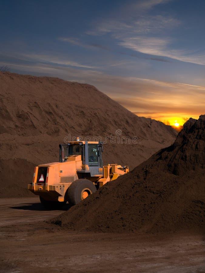 Den stora backhoen och överkanten smutsar staplar på solnedgångsoluppgången arkivfoto