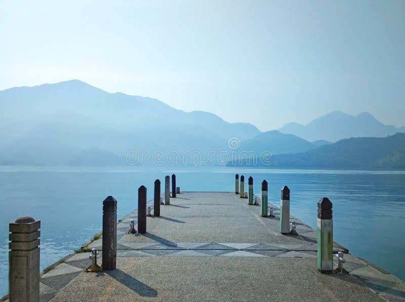 Den stora blåa sjön withwooden pir i morgonen royaltyfri fotografi