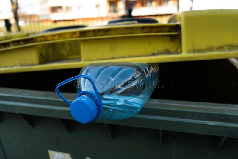 Den stora bl?a plast- flaskan i ett gult gr?nt avfallfack - ?teranv?nd f?r natur arkivfoton