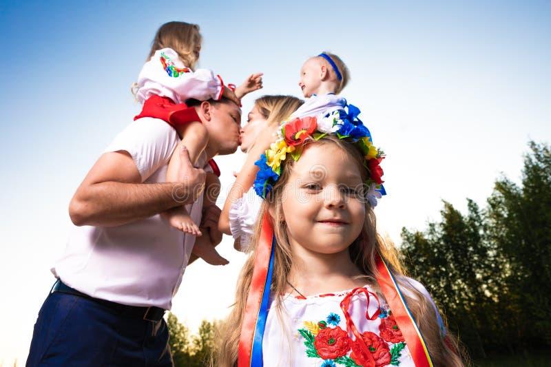 Den stora familjen i etniska ukrainska dräkter sitter på ängen, begreppet av en stor familj arkivbild