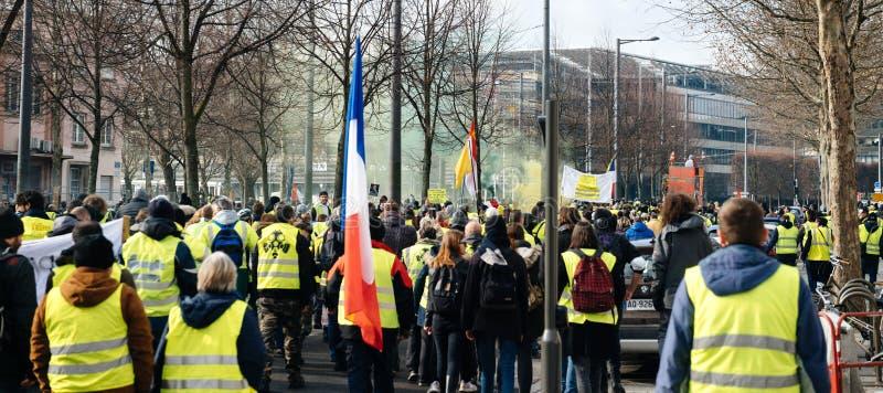Den stora folkmassan av västar för den franska gatan för folk gula protesterar royaltyfria bilder