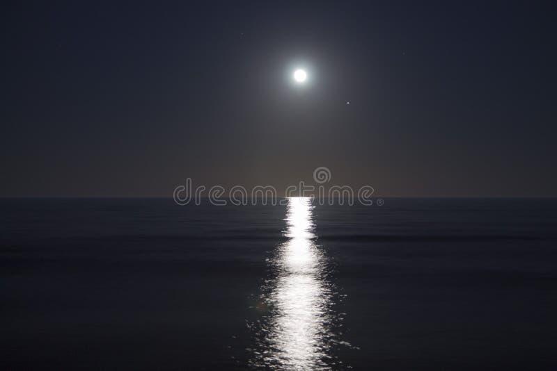 Den stora fullmånen stiger ovanför havet på natten Mån- ljus reflekterat på vattnet Mån- bana hav royaltyfria foton