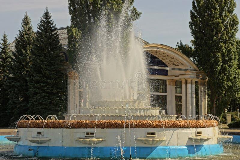 Den stora gamla springbrunnen med strålar och färgstänk av vatten i parkerar med gröna träd arkivbilder