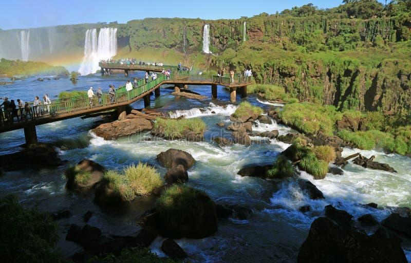 Den stora gruppen av besökaren på strandpromenaden bland den kraftiga strömmen, Iguazu Falls på den brasilianska sidan, Foz gör I royaltyfria foton