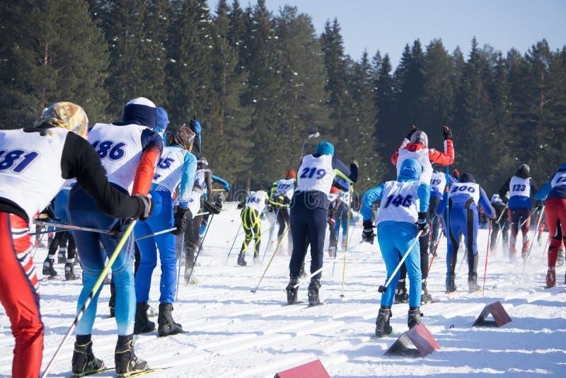 Den stora gruppen av skidåkare skidar på lutningar i en bergsemesterort i vinter arkivfoton