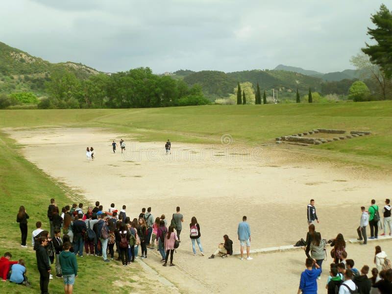 Den stora gruppen av studenter tycker om att besöka den gamla stadion av forntida Olympia, UNESCOvärldsarv i Grekland royaltyfri bild