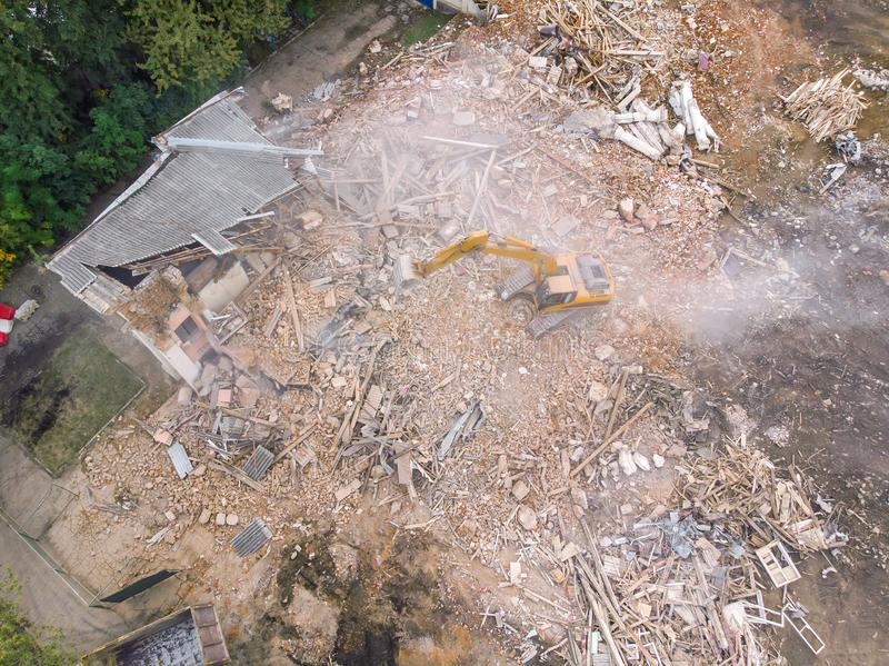 Den stora gula grävskopan som ut gör klar platsen från, fördärvar och skräp royaltyfria foton