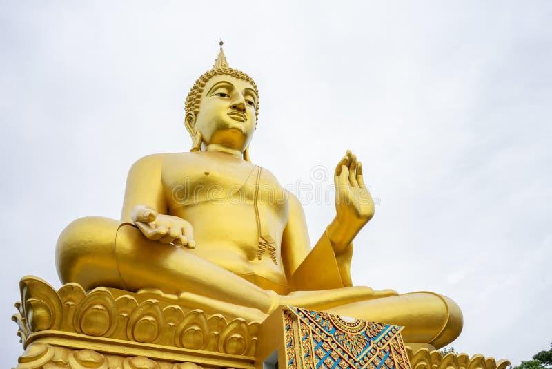 Den stora guld- Buddhastatyn står högväxt och står ut och respekteras av buddister Är tinget som rymmer många personer arkivbild